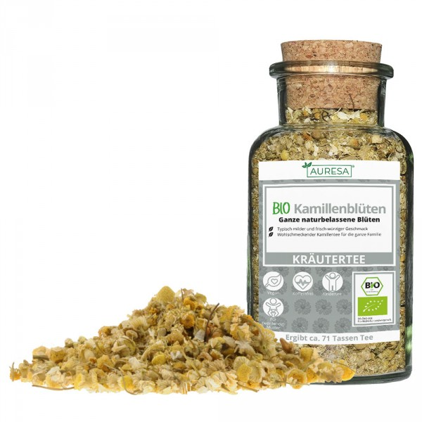 Loose organic chamomile flowers in a glass